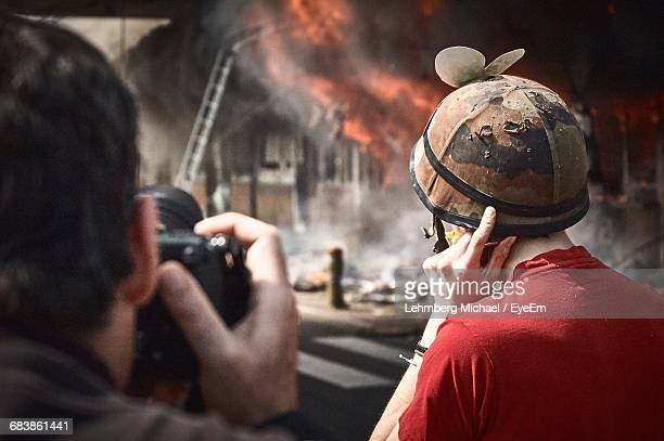 rear view of photographer and journalist watching building set on fire - journalist stock pictures, royalty-free photos & images