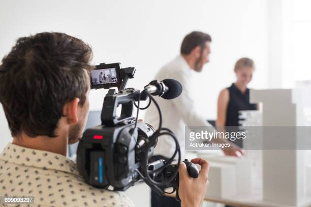 Rear view of photographer video recording business people in office