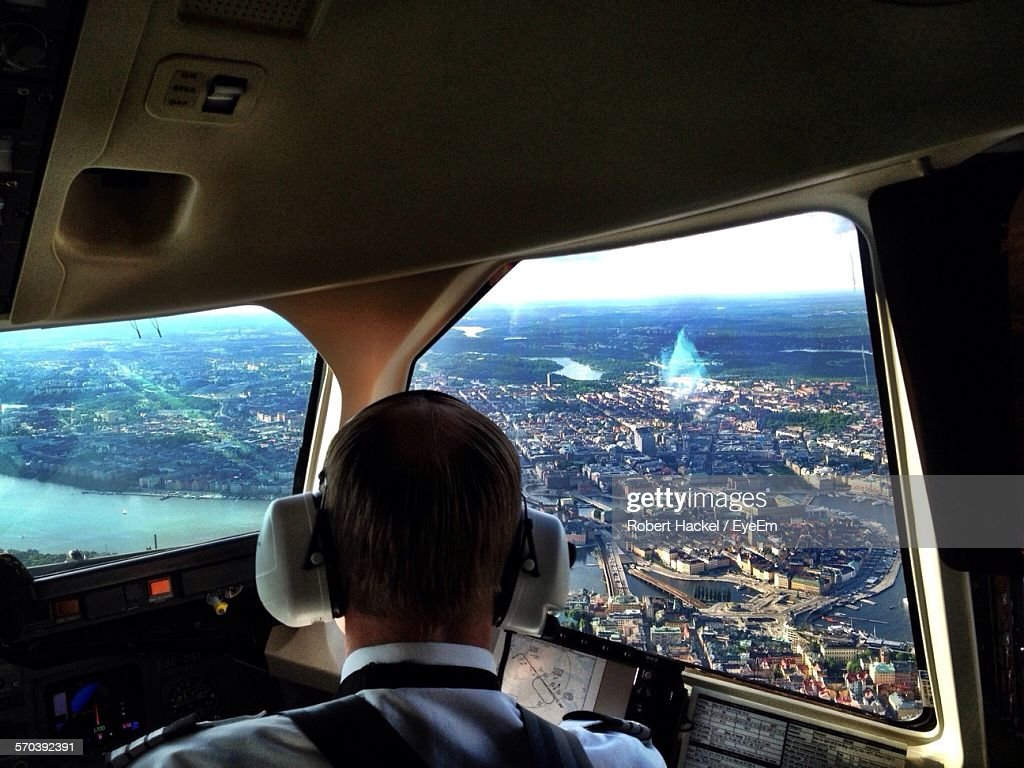 Rear View Of Pilot In Airplane Looking At City View Through Window : Foto de stock