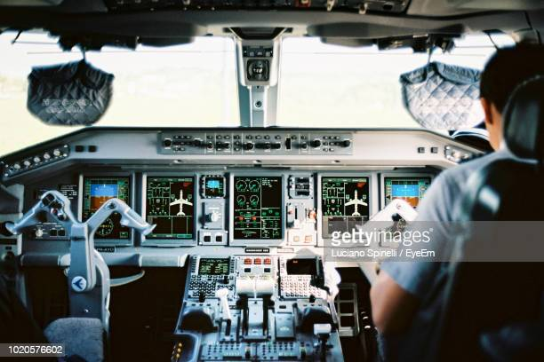 rear view of pilot sitting in cockpit - cockpit stock pictures, royalty-free photos & images