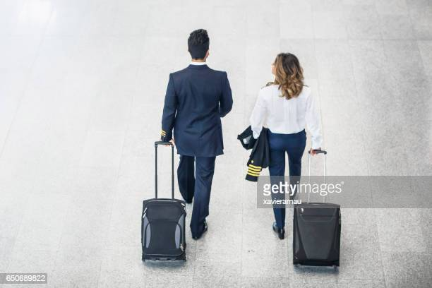 Rear view of pilots walking on airport floor