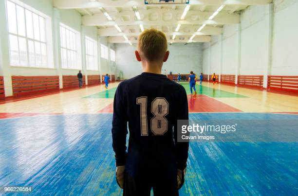 rear view of player standing at indoor soccer court - portiere posizione sportiva foto e immagini stock