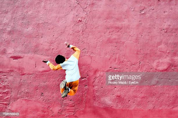 Rear View Of Playful Boy Jumping Against Old Red Wall
