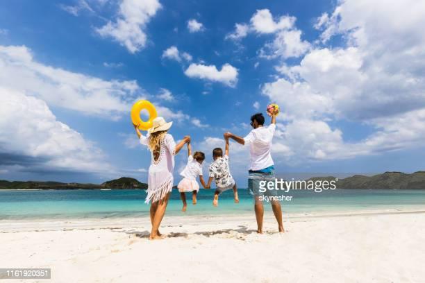 vista trasera de la familia juguetona divirtiéndose en el día de verano en la playa. - lombok fotografías e imágenes de stock