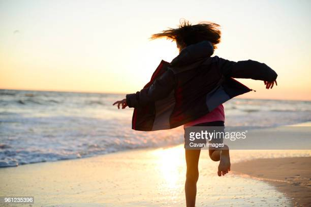 rear view of playful girl running on shore against clear sky during sunset - destin beach stock pictures, royalty-free photos & images