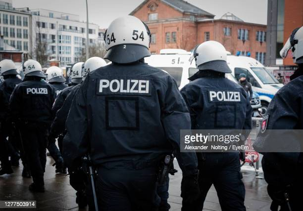 rear view of police force walking on street in city - police force stock pictures, royalty-free photos & images