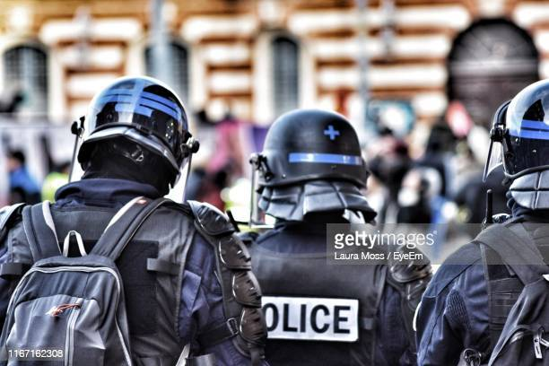 rear view of police in uniforms standing outdoors - france stock pictures, royalty-free photos & images