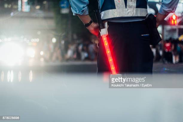 Rear View Of Police Man With Illuminated Stick