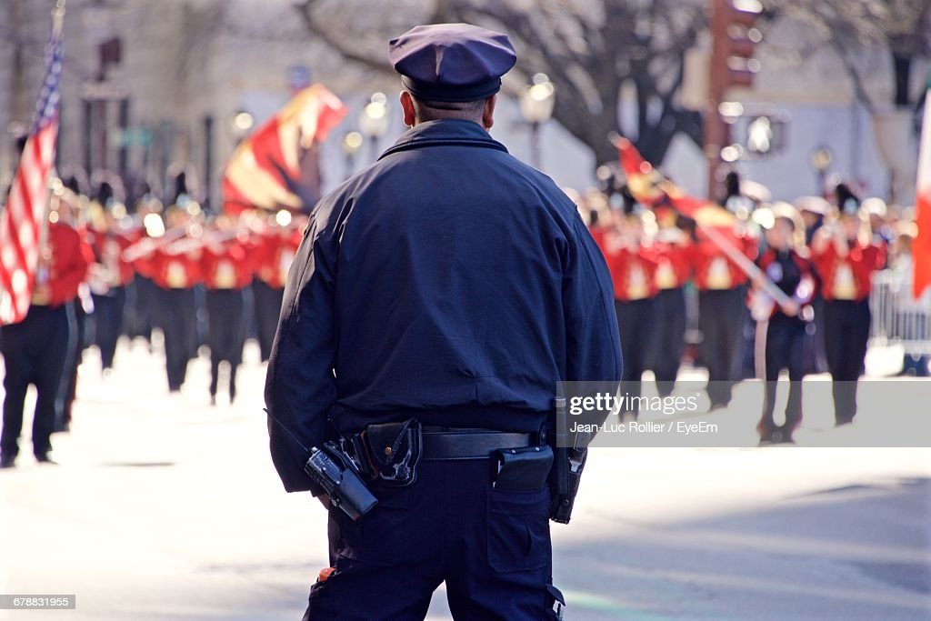 Rear View Of Police Officer Standing On Road Looking At St Patricks Day Parade : Stock Photo