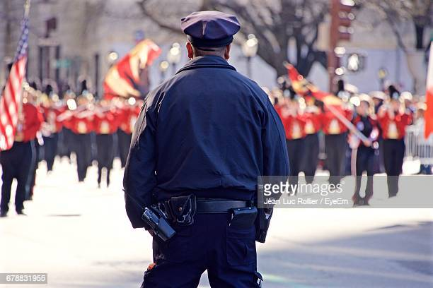 rear view of police officer standing on road looking at st patricks day parade - uniform cap stock pictures, royalty-free photos & images