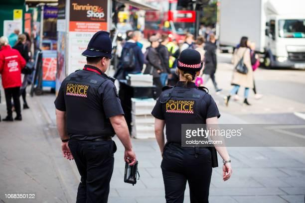 ロンドン市内の路上人の警官の後姿 - ロンドン市 ストックフォトと画像