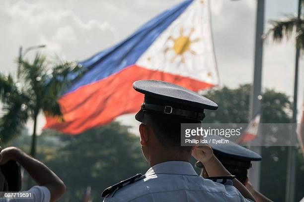 rear view of police saluting philippines flag - philippines flag stock pictures, royalty-free photos & images