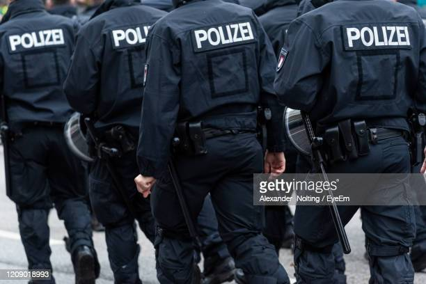 rear view of police walking on land - allemagne photos et images de collection