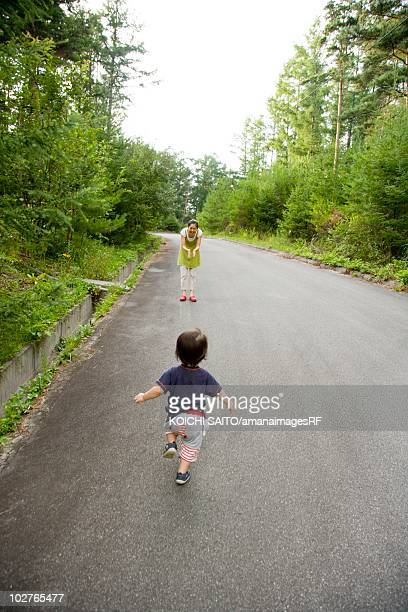 Rear view of preschool age child running toward his mother