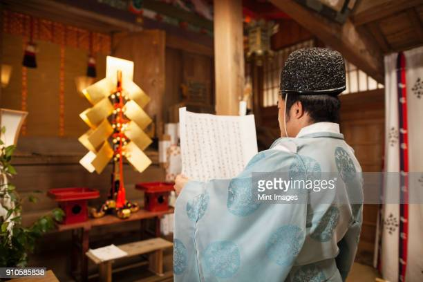 rear view of priest holding scroll at shinto sakurai shrine, fukuoka, japan. - shrine stock pictures, royalty-free photos & images