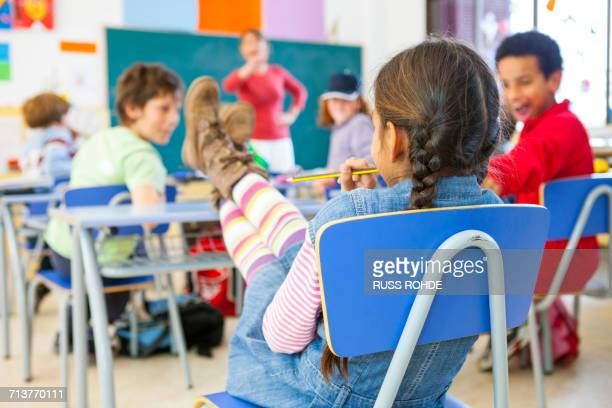 Rear view of primary schoolgirl with feet on desk in classroom