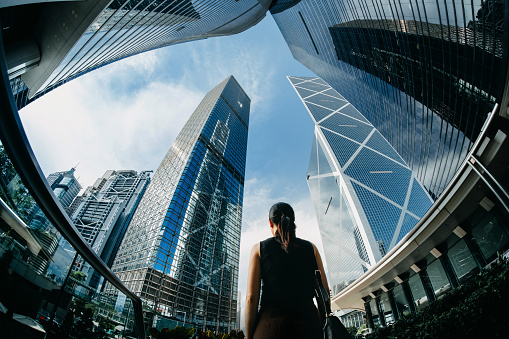Rear view of professional young businesswoman standing against contemporary financial skyscrapers in downtown financial district and looking up into sky with positive emotion - gettyimageskorea