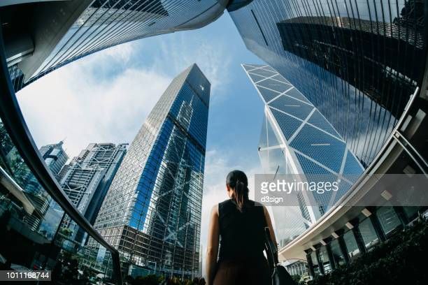 rear view of professional young businesswoman standing against contemporary financial skyscrapers in downtown financial district and looking up into sky with positive emotion - wolkenkrabber stockfoto's en -beelden
