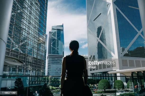 rear view of professional young businesswoman standing against contemporary financial skyscrapers in downtown financial district and looking up into sky with positive emotion - la via giusta foto e immagini stock