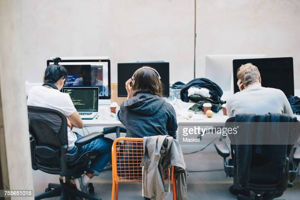 Rear view of programmers using computers at desk in office