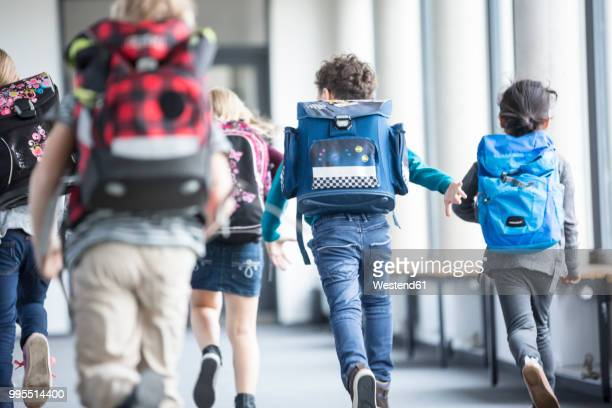 rear view of pupils rushing down school corridor - schulkind stock-fotos und bilder
