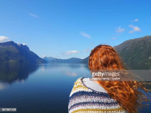 rear view of redhead woman looking at lake against blue sky - lake auburn stock photos and pictures