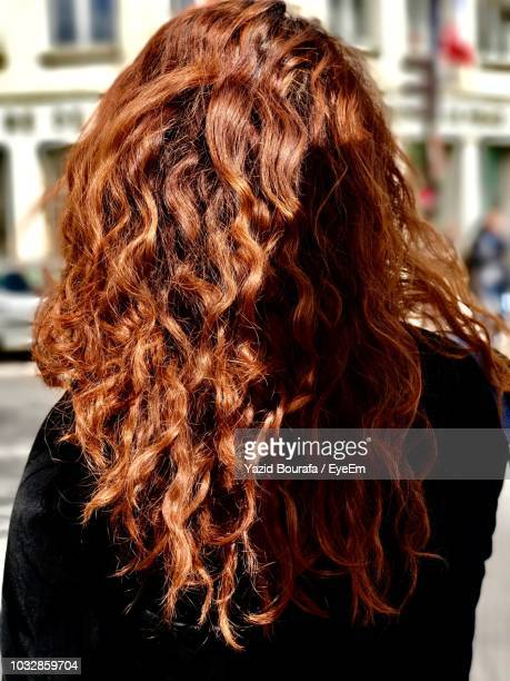 rear view of redhead woman standing on street - curly stock pictures, royalty-free photos & images