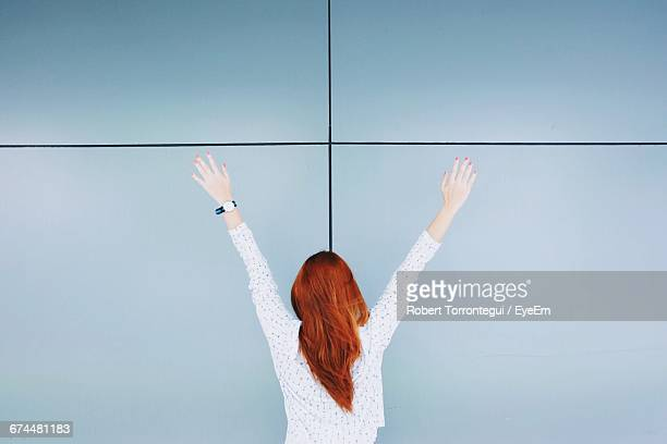 Rear View Of Redhead Woman With Arms Raised