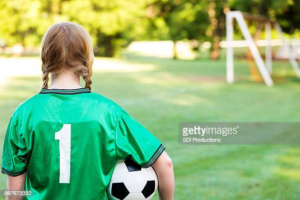 Rear view of reflective soccer player thinking about the game