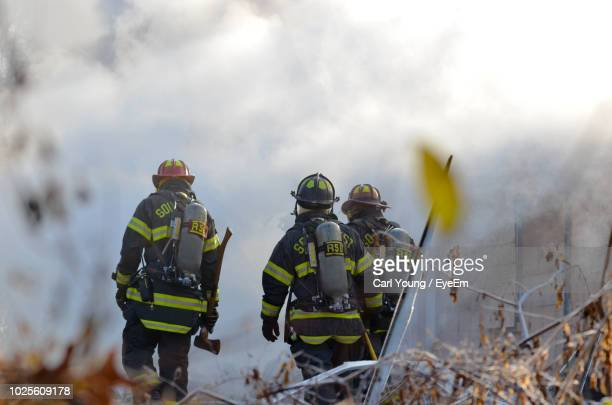 rear view of rescue workers - firefighter stock pictures, royalty-free photos & images
