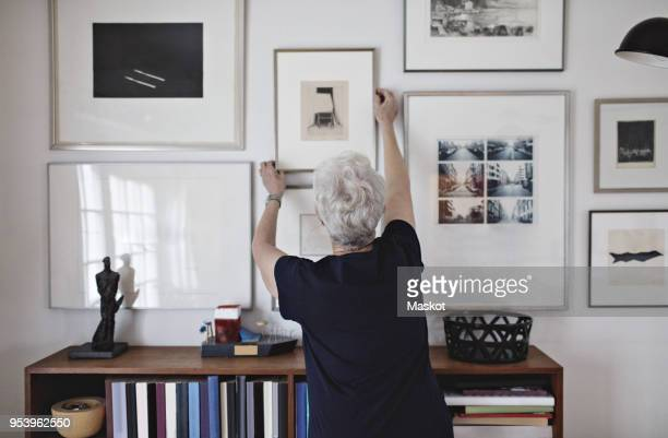 Rear view of retired senior woman adjusting picture frame on wall over bookshelf at home
