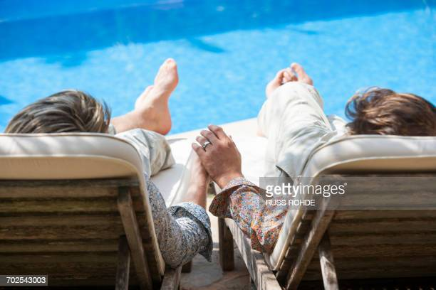Rear view of romantic male couple holding hands at poolside, Majorca, Spain
