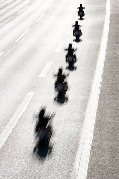 Rear view of row of motorcycle riders on highway, elevated view