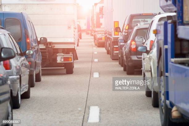 rear view of rows of traffic queueing on highway - traffico foto e immagini stock