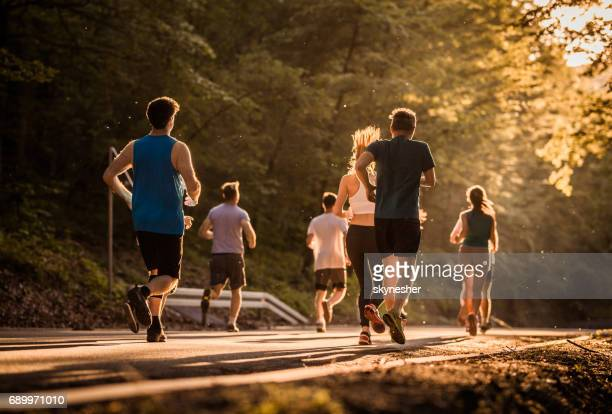 Rear view of runners during a marathon race at sunset.