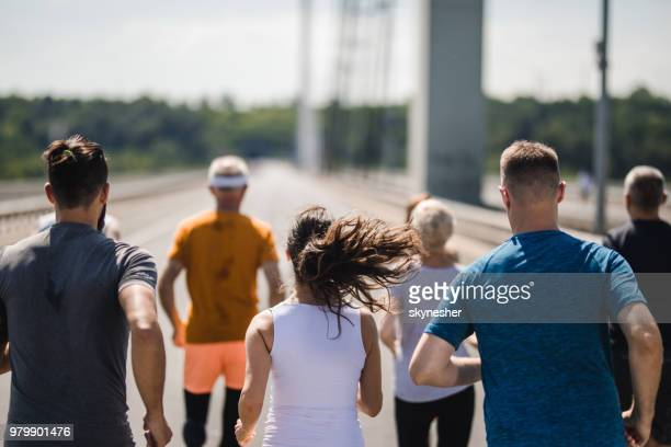 rear view of running a marathon on the road! - marathon stock pictures, royalty-free photos & images