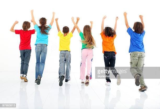 rear view of running children. - skipping along stock pictures, royalty-free photos & images