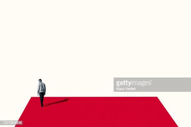 rear view of sad young man walking on red ramp - zweifarbig farbe stock-fotos und bilder