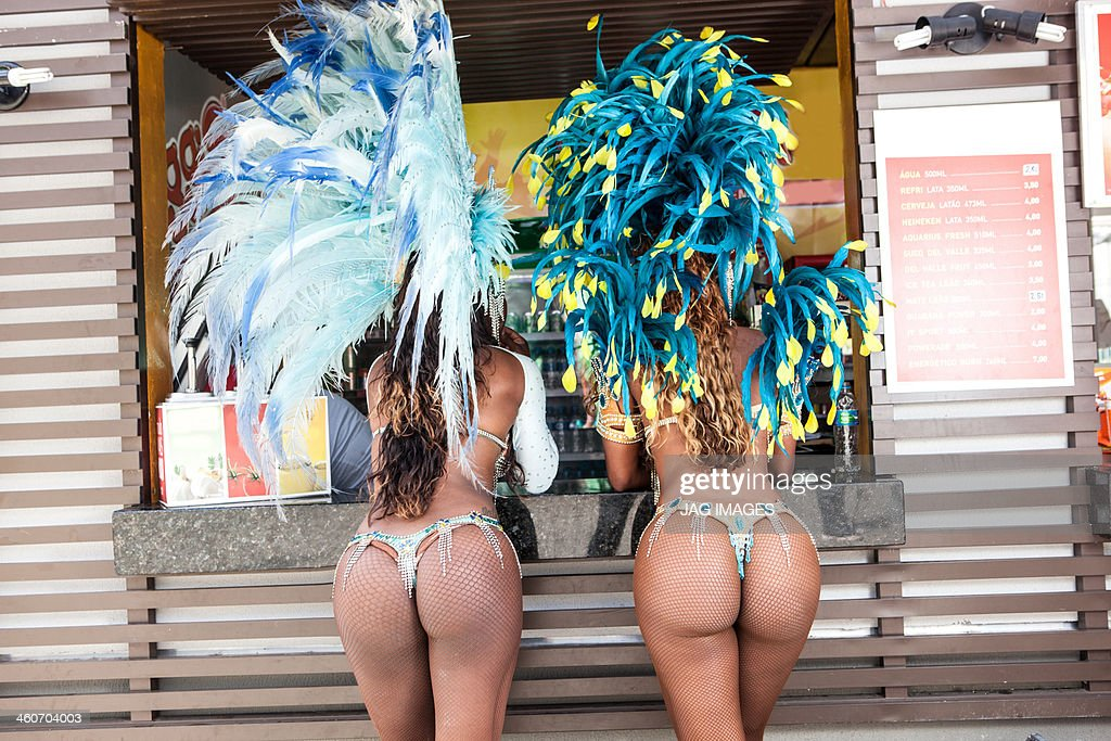 Rear view of samba dancers in costume by food stall, Rio De Janeiro, Brazil : Stock Photo