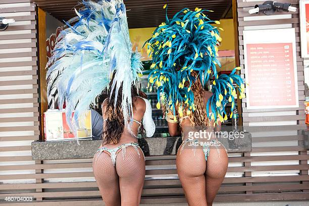rear view of samba dancers in costume by food stall, rio de janeiro, brazil - woman bum stock photos and pictures