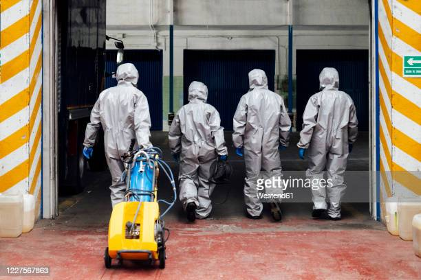 rear view of sanitation coworkers entering warehouse with decontamination chemical - protective suit stock pictures, royalty-free photos & images
