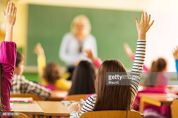 Vista traseira de escola crianças levantar as mãos na escola.