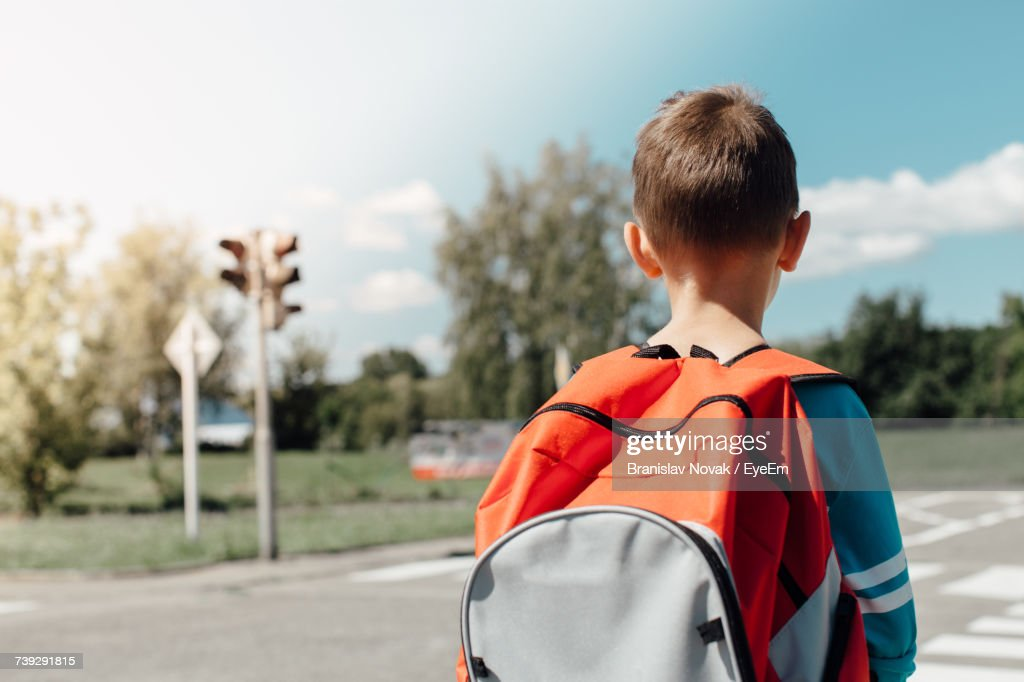 Rear View Of Schoolboy Carrying Backpack While Standing On Road : Stock-Foto