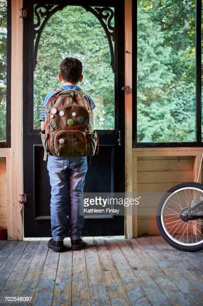 Rear view of schoolboy looking through porch window