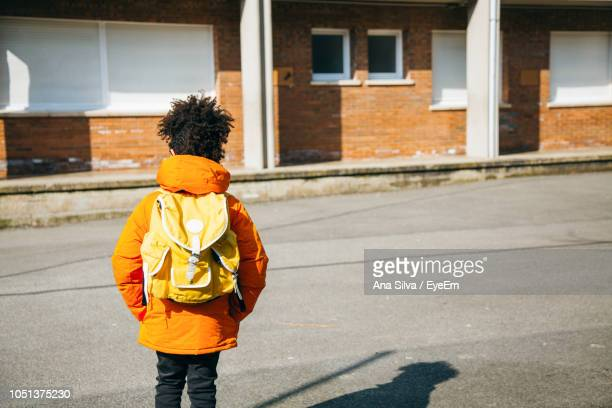 Rear View Of Schoolboy Standing On Street During Sunny Day