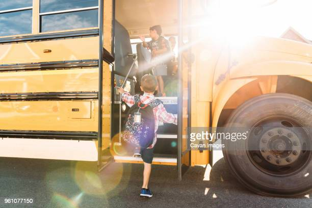 rear view of schoolboy stepping on bus - stepping stock pictures, royalty-free photos & images