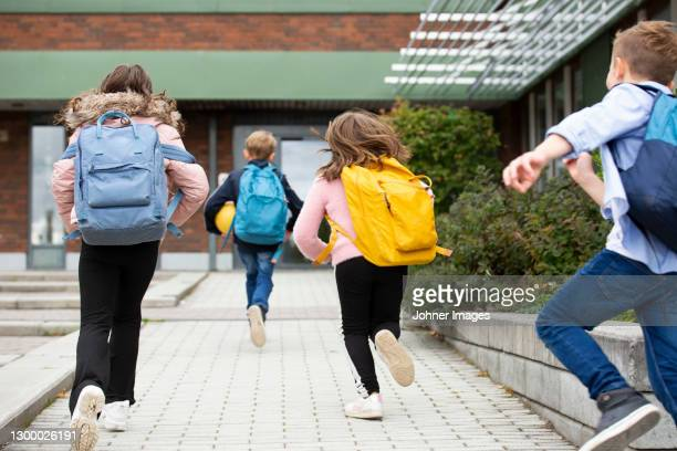 rear view of schoolchildren running - education stock pictures, royalty-free photos & images