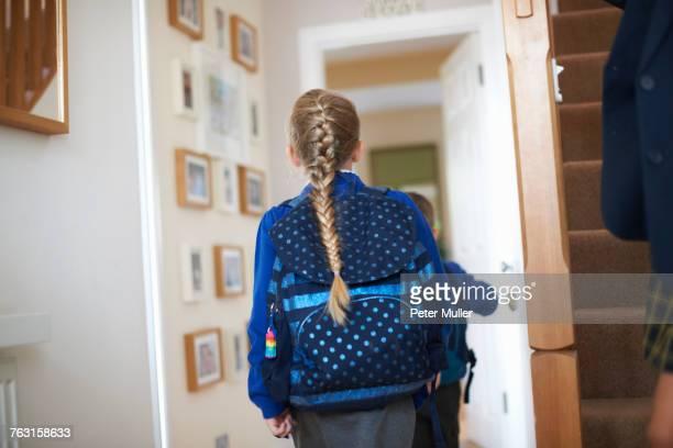 Rear view of schoolgirl in uniform in hallway