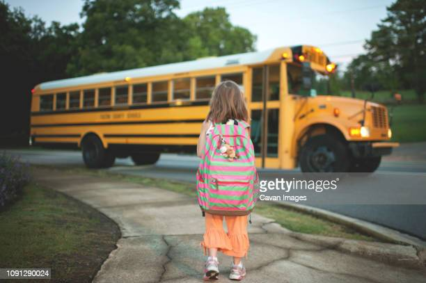 rear view of schoolgirl with backpack waiting for bus while standing on footpath - school bus stock pictures, royalty-free photos & images