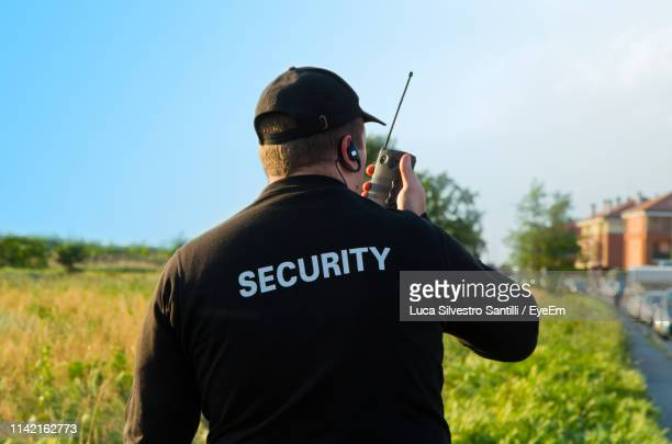rear view of security guard talking on walkie-talkie at field - watchmen stock pictures, royalty-free photos & images